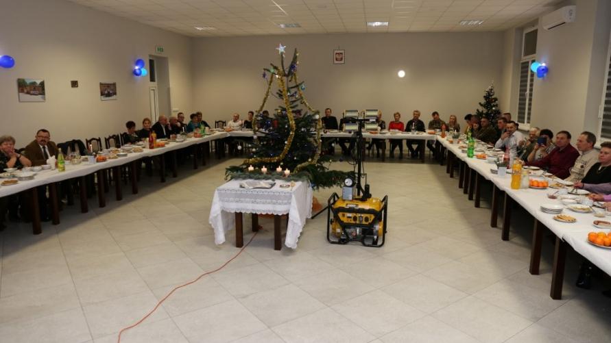 Sala z gośćmi zasiadającymi przy stołach.