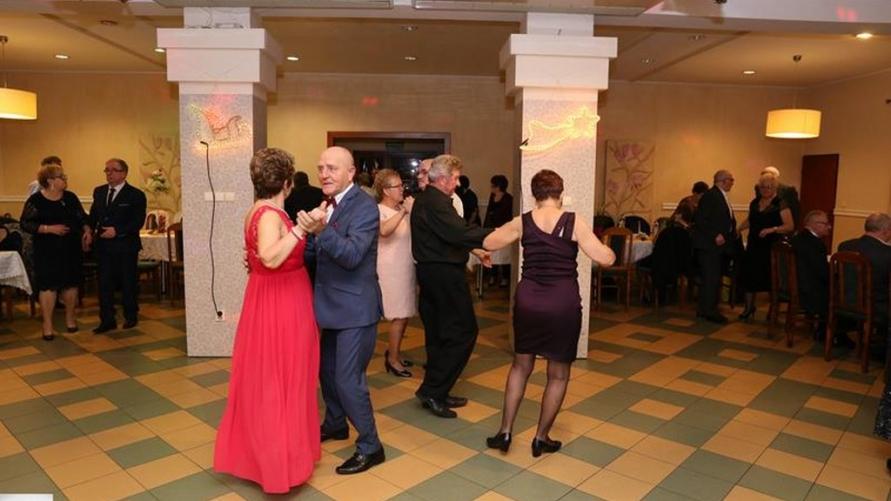 Zdjęcie sali z tańczącymi gośćmi.