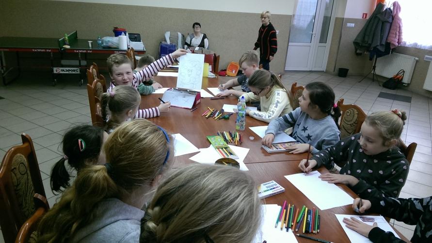 Dzieci przy stole rysują na kartkach.