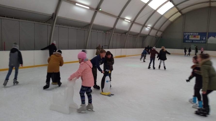 Dzieci jeżdżą na łyżwach na krytym lodowisku.