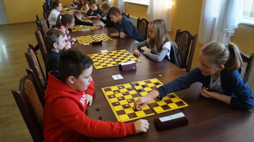 Rozgrywki przy stołach dzieci w warcaby.