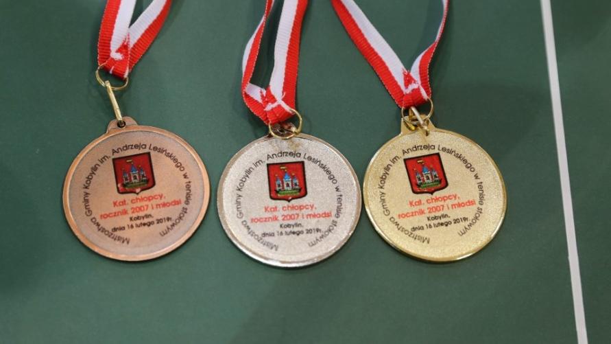 3 medale położone na stole tenisowym.