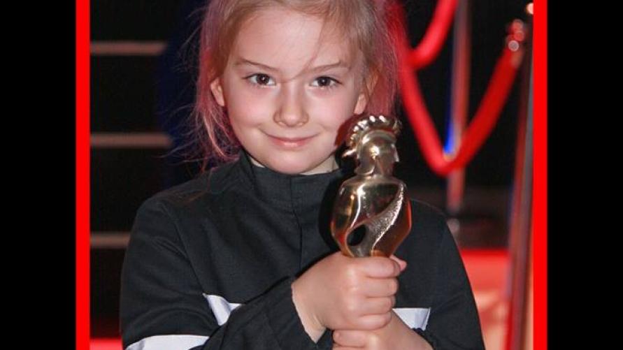 """Widok dziewczynki trzymającej statuetkę """"oskara"""" i napis """" FLORIANY 2019 może to Wasza OSP zdobędzie strażackiego Oscara?"""