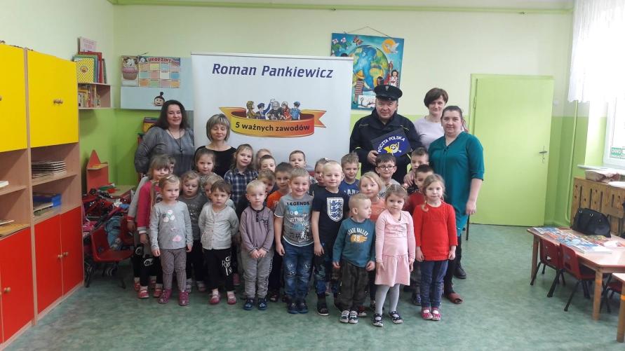 """Zdjęcie grupowe w klasie na tle bilbordu z napisem """"Roman Pankiewicz"""""""