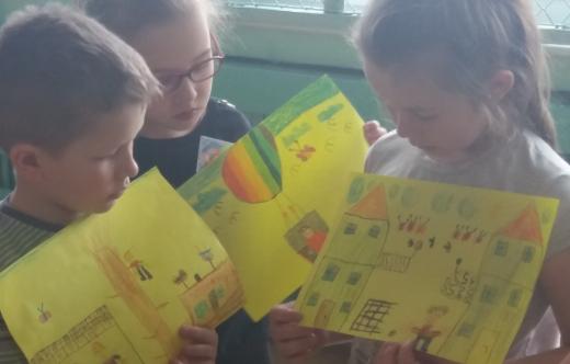 Dzieci w bibliotece trzymające rysunki.