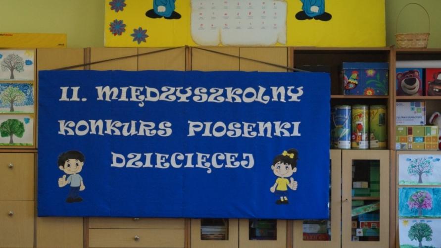 """Widok zawieszonej tablicy w klasie na szafach z napisem """"II MIĘDZYSZKOLNY KONKURS PIOSENKI DZIECIĘCEJ"""" na fioletowym tle."""