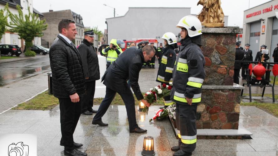 strażacy OSP Kobylin przed pomnikiem św. Floriana