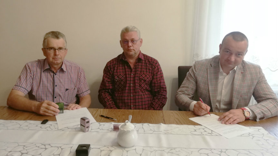 Na zdjęciu jest trzech mężczyzn. Podpisują umowę