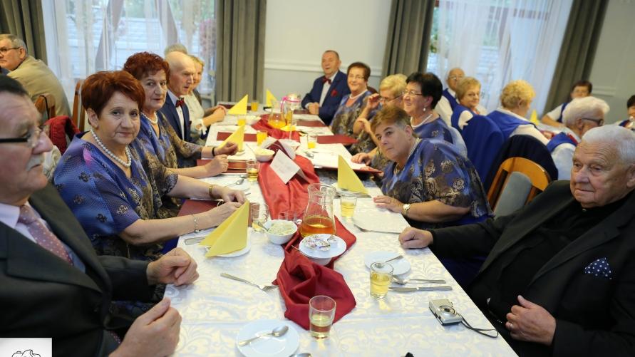 Siedzący goście przy stołach.