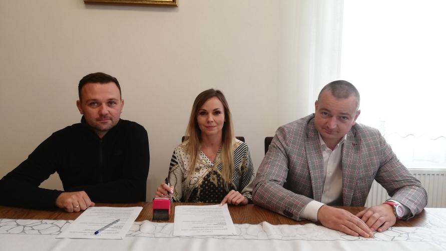 Trzy dorosłe osoby siedzą przy stole