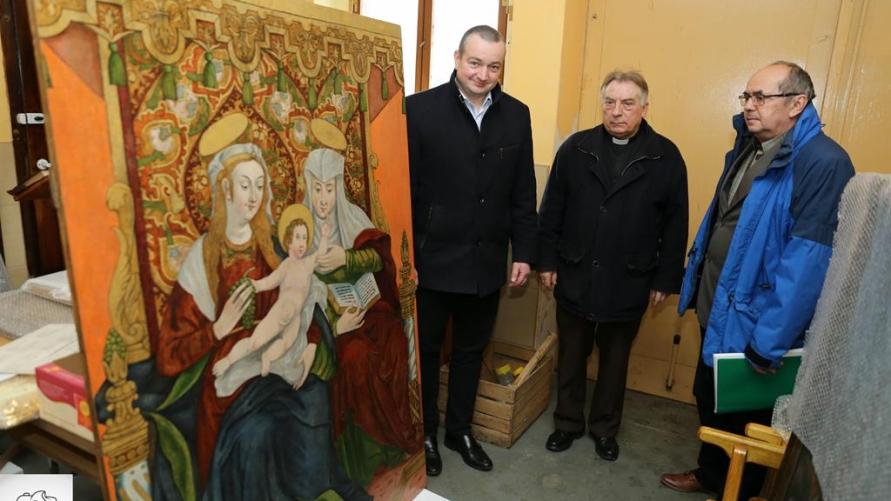 Proboszcz R. Muszyński, Burmistrz T. Lesiński i P. Wasielewski przy odrestaurowanym obrazie.