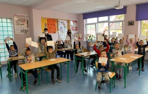 Dzieci siedzące w klasie w ławkach i unoszące do góry ręce z kartkami.