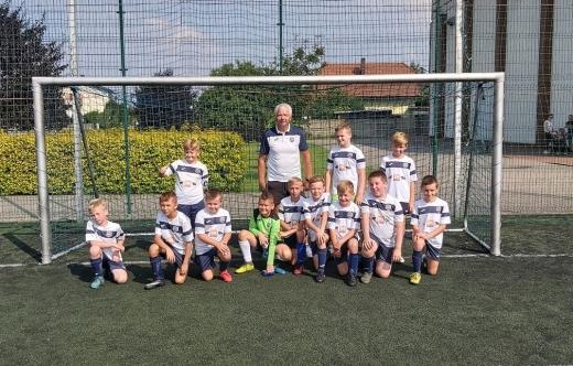 Grafika przedstawia zawodników oraz trenera na tle bramki piłkarskiej.